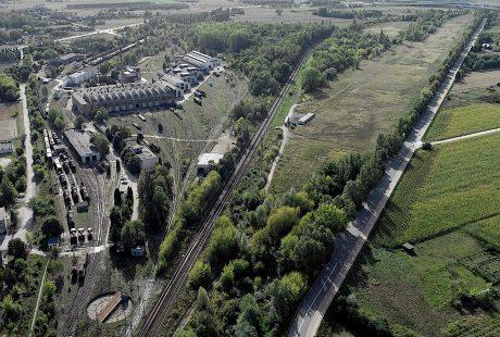 Zdjęcie przedstawia widok terenu, na którym miał być zbudowany port przeładunkowy w Karsznicach. Jest to widok zielonej trawy, krzewów i linii kolejowych oraz zabudowań z lotu ptaka.