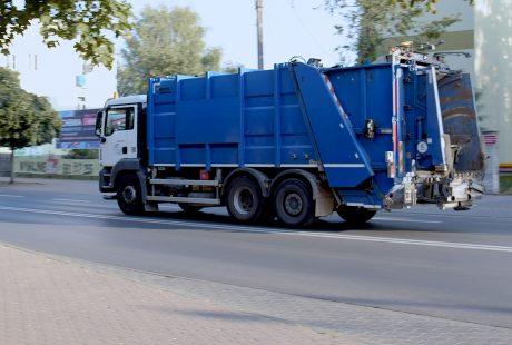 Niebieski samochód - śmieciarka na asfaltowej ulicy.