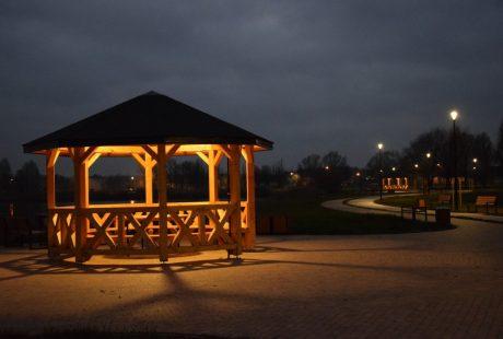 Na zdjęciu widać drewnianą altanę i oświetlone chodniki przy zbiorniku wodnym Kępina