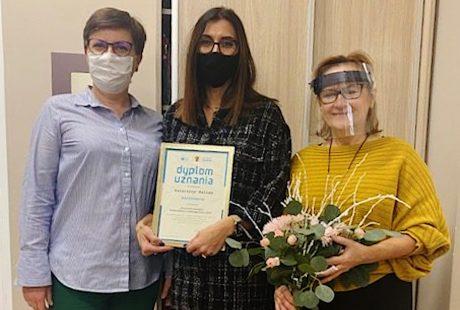 Na zdjęciu widać trzy kobiety, które stoją. Jedna trzyma bukiet kwiatów, a stojąca pośrodku obrazek, na którym jest napisane dyplom uznania.
