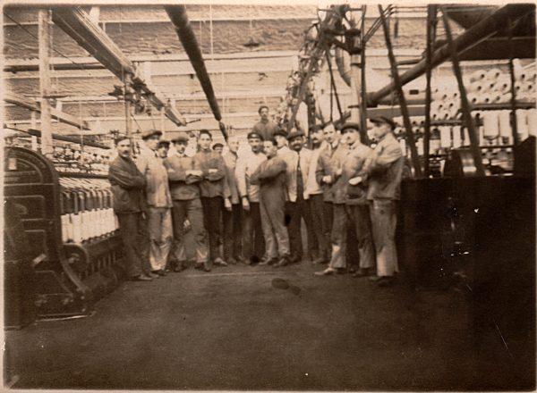 Historyczne zdjęcie wnętrza fabryki z pozującymi pracownikami