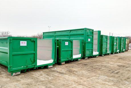 Zielone kontenery na odpady, na zaśnieżonym placu.