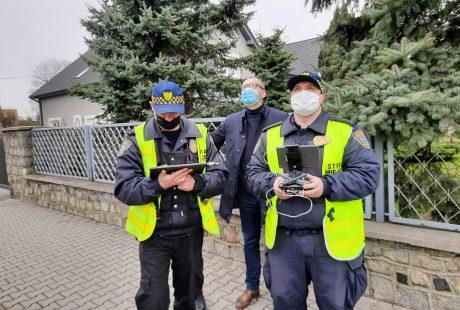 Strażnicy miejscy nawigują dron, akcji przygląda się prezydent Konrad Pokora