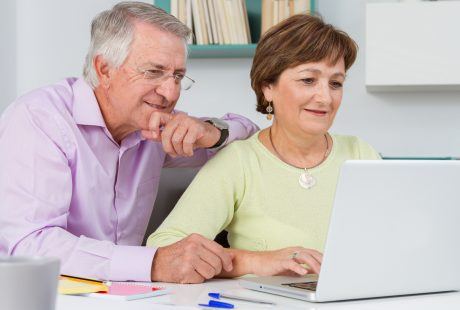 Para seniorów pracuje na komputerze przenośnym