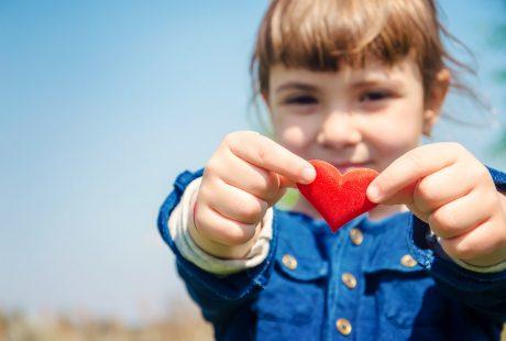 Dziewczynka w wyciągniętych przed siebie rękach trzyma małe czerwone serduszko