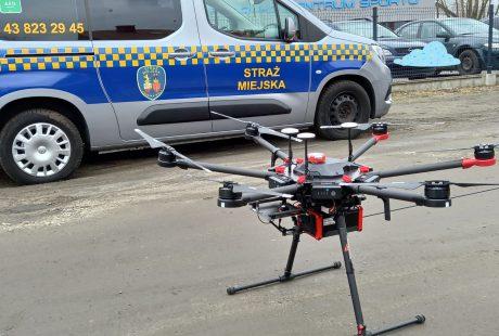Dron z bliska na tle samochodu Straży Miejskiej