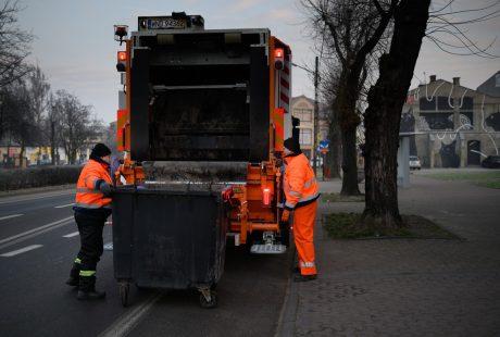 Dwóch ładowaczy zaczepia kontener ze śmieciami na podnośniku śmieciarki