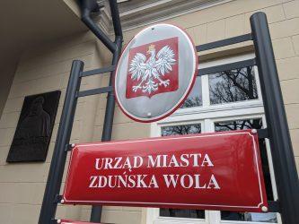 Na zdjęciu znajduje się fragment budynku urzędu miasta zduńska wola, przed którym stoi czerwona tablica urzędowa z napisem urząd miasta zduńska wola