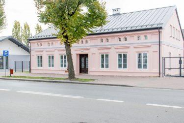Na zdjęciu widać ulicę oraz stojący przy niej różowy niski budynek Inkubatora Inicjatyw Społecznych.